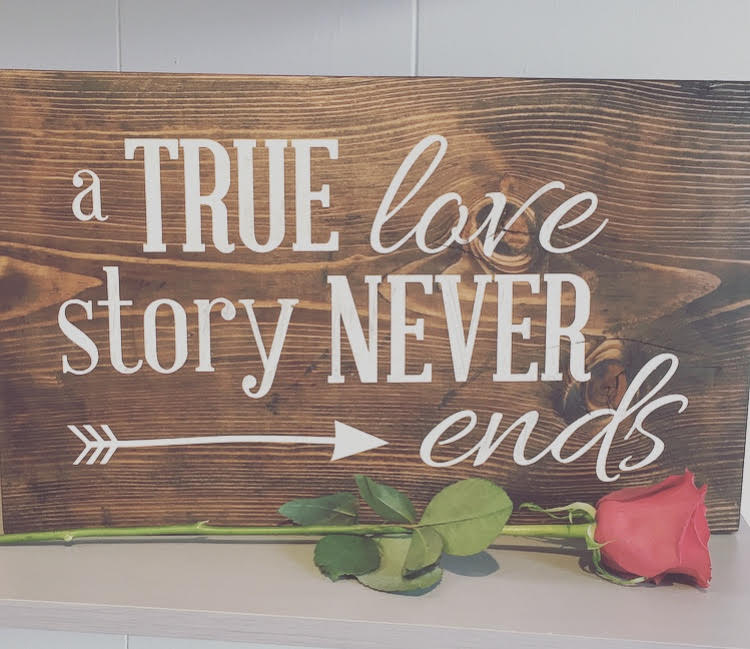 Wood board with the quote a true love story never ends painted on it